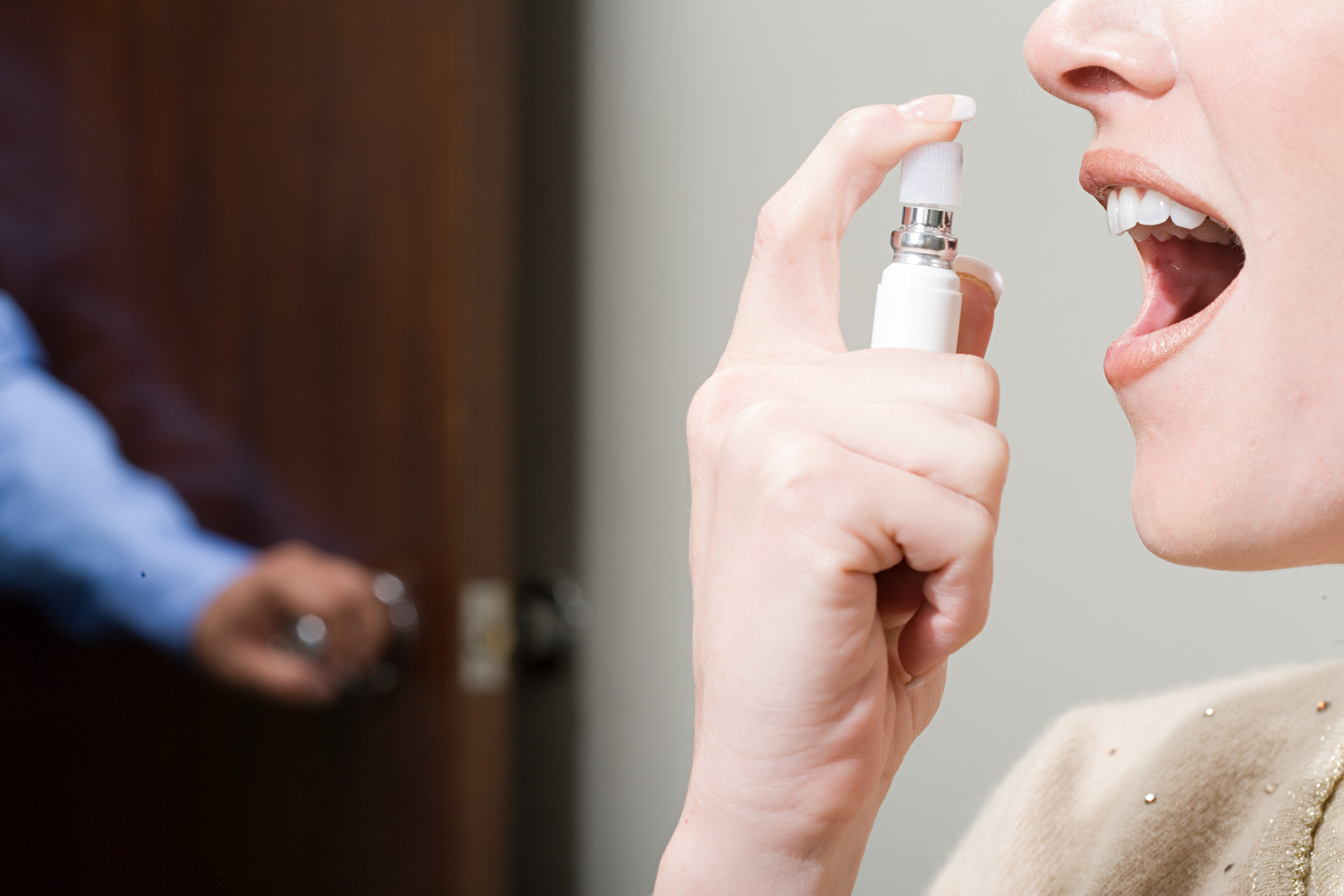 Woman Spraying Breath Freshener