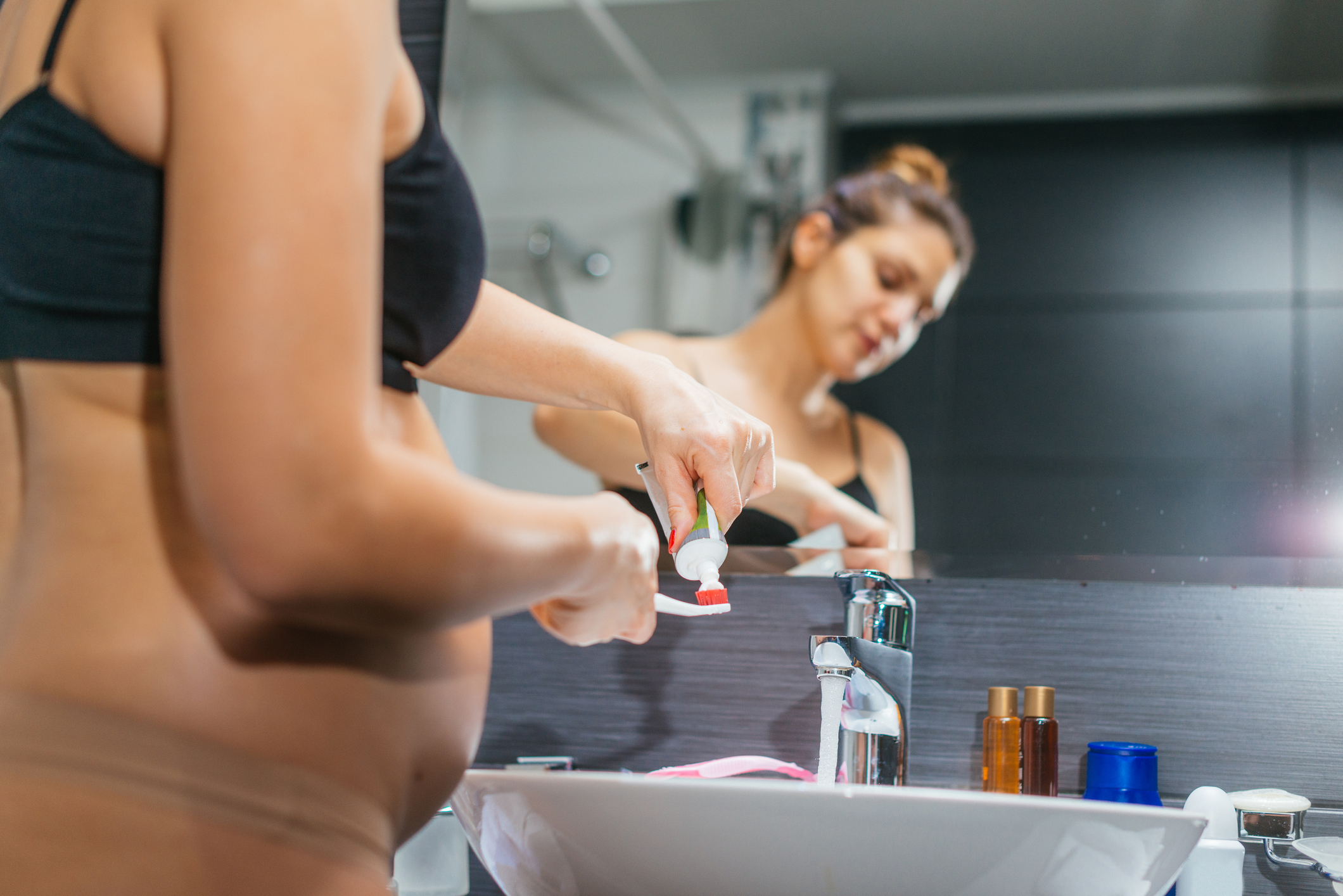 Pregnant Woman In Bathroom Brushing Her Teeth